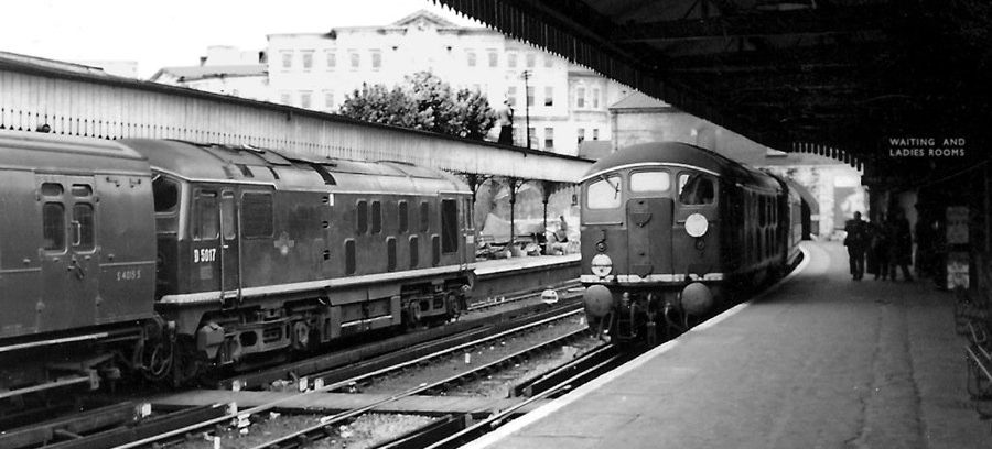 The date is July 13th, 1961 and the location is Maidstone East station with the Old Sessions House (now County Hall) dominating the background. At this time, this was the limit of third rail on the line to the coast, the new electrification onwards not being completed until October 9th. Athermos axlebox-fitted No. D5017 is on a Down train formed of Bulleid steam-heated stock (S4015S leading), as sister Type 2 No. D5007 draws into the station with a service from Ashford. Photo: Ian Cuthbertson collection